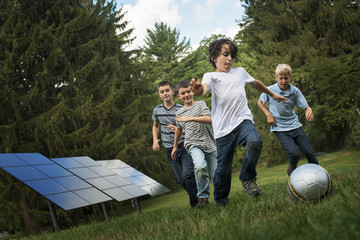 A group of boys running after a ball past solar panels in the woods.