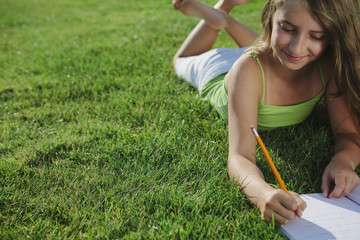 Smiling nine year old girl sitting on grass, writing in notebook