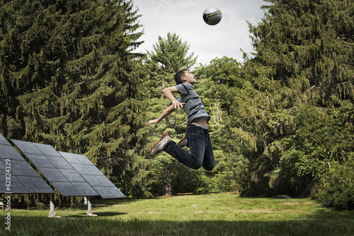A boy leaping to head a ball. Solar panels in background