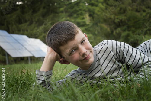 A boy lying in the grass, beside solar panels.