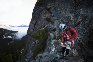 A rock climber stands on the summit of a peak after climbing to the top with the aid of a rope.