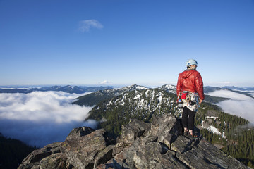 A rock climber stands on the summit of a peak after climbing to the top with the aid of a rope and protection.