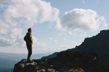 Male hiker standing on rocky cliff, facing overlook, dusk