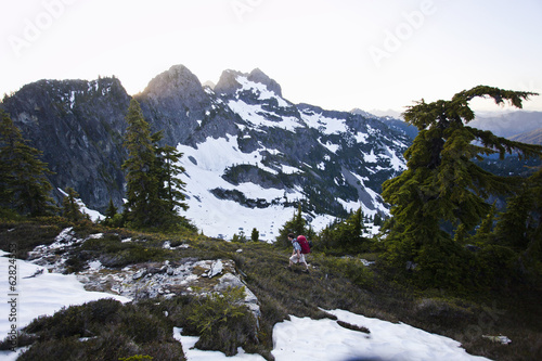 A young man hikes around a snow patch while going to the summit of a large mountain in the Cascades of Washington, USA.