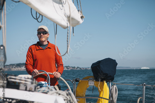 Middle aged man steering sailboat on Puget Sound, Washington, USA