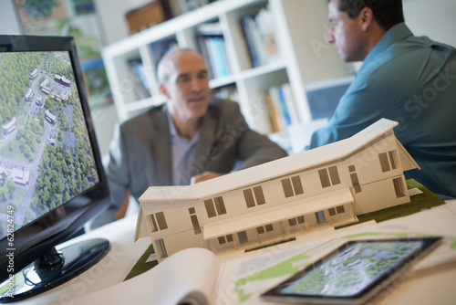 Architects working on a green construction project, using computer technology, in an office. Scale model of a building.