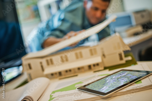 Architects working on a green construction project, using computer technology, in an office. An architect's model of a house. Computer tablet.