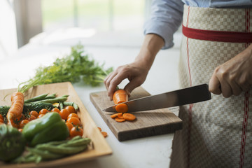 A woman preparing fresh vegetables. Slicing a carrot.