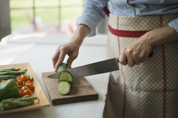A  woman slicing organic vegetables. Cucumbers.