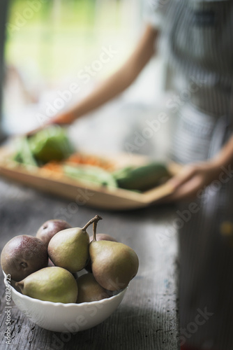 A person preparing organic vegetables in a kitchen. Tray of vegetables. Bowl of pears.