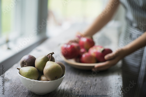 A person preparing organic fresh produce in a kitchen. Apples.  Bowl of pears.
