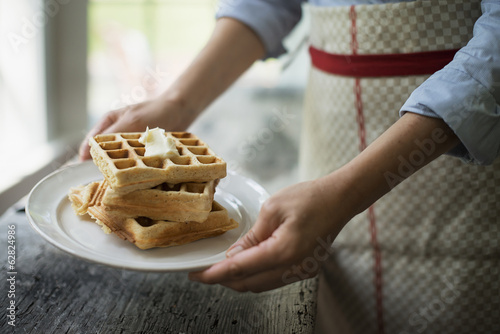 A woman holding a plate of fresh cooked waffles, with cream on top.