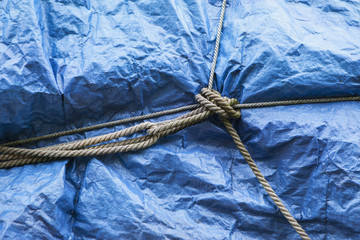 A blue tarpaulin covering stacked commercial fishing nets on the dockside at Fisherman's Wharf, Seattle.