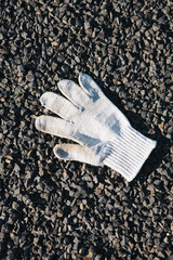 Discarded white glove on the ground.