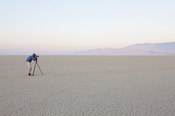 Man with camera and tripod on the flat saltpan or playa of Black Rock desert, Nevada.