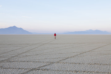 A man in the flat playa, salt pan, of Black Rock Desert, Nevada.