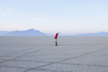 A man with arms raised, in the dawn light in Black Rock Desert, Nevada.