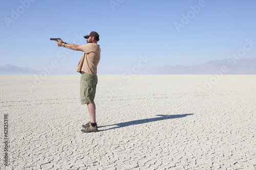 A man aiming a hand gun, holding it with his arm outstretched, standing in a vast, barren desert.
