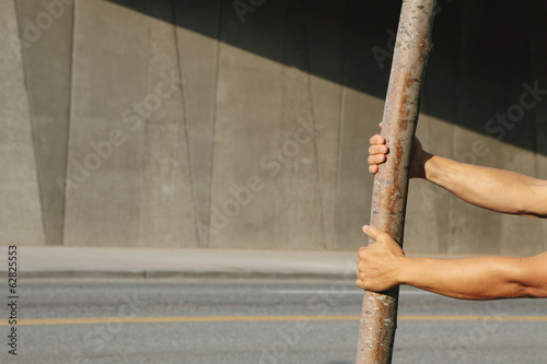 Man pulling on a small tree, on a city sidewalk.