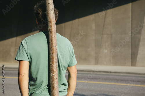 Man leaning against small tree, city street in background