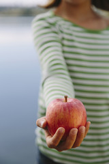 Detail of nine year old girl holding organic apple