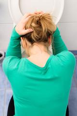 Frau kniet vor einer Toilette