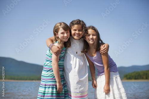 Three young girls, friends, hugging each other and smiling.