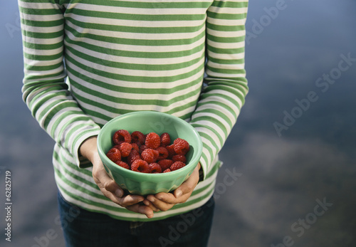 Nine year old girl holding bowl of organic raspberries