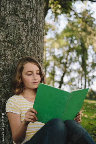 Nine year old girl sitting beneath tree, reading book