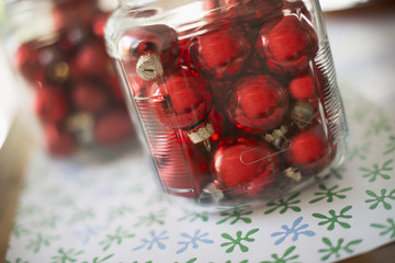 Red glass ball Christmas ornaments in glass jars on a tabletop.
