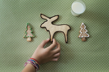 A girl's hand arranging an organic homemade Christmas cookies in the shape of a reindeer and Christmas trees.