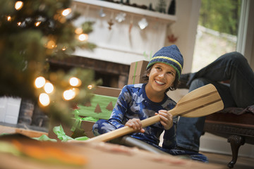 A boy by a Christmas tree unwrapping a gift, a wooden oar.