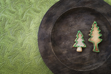 Organic homemade Christmas cookies in the shape of Christmas trees on a round wooden plate.