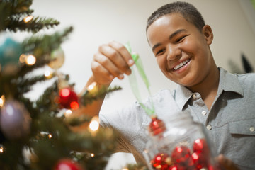 A young boy holding Christmas ornaments and placing them on the Christmas tree.