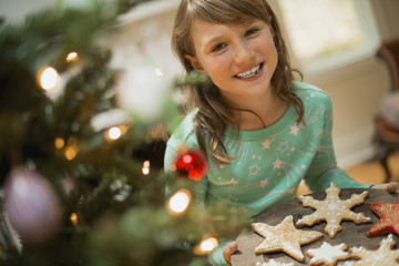 A young girl with a tray of organic baked and iced Christmas cookies.