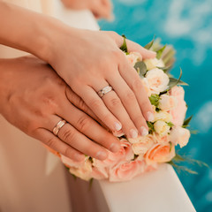 Wedding rings with bouquet near the sea