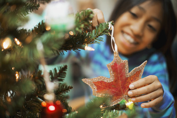 A young girl placing a handmade Christmas ornament in the shape of a maple leaf on a Christmas tree.