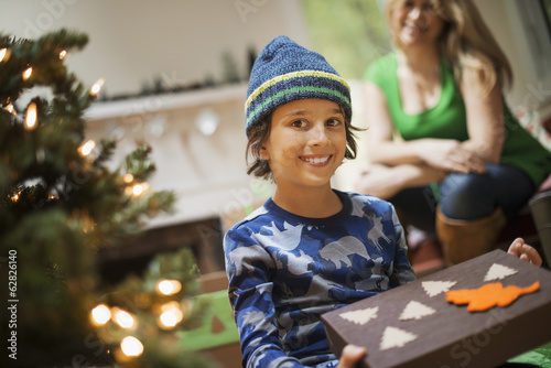 A boy with a Christmas present, gift wrapped in a box with recycled Christmas packaging.