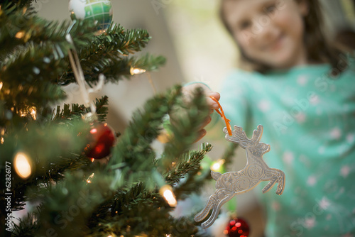 A young girl placing a homemade Christmas ornament on a tree.
