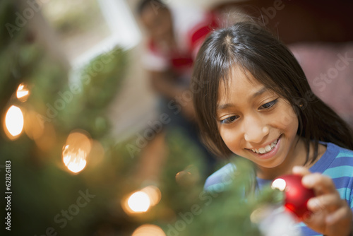 A girl placing a handmade ornament on a Christmas tree.