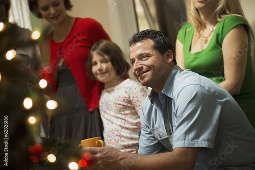 A Christmas gathering, adults and children in a room around a Christmas tree, celebrating together.
