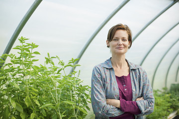 A woman working at an organic farm, in the greenhouse or polytunnel.