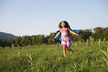 A young girl running across a field, wearing fabric butterfly wings.