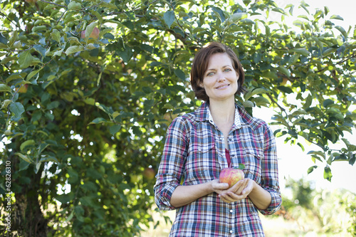A woman in a plaid shirt holding a large freshly picked apple, in the orchard at an organic fruit farm.