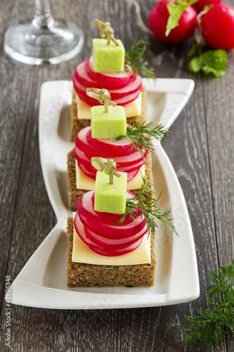 Appetizer of black bread with radish and cheese.