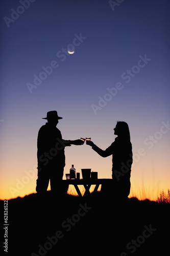 Guests at Wolwedans at sunset. Silhouette of two people, a couple, raising glasses in a romantic toast in NamibRand Nature Reserve, Namibia.
