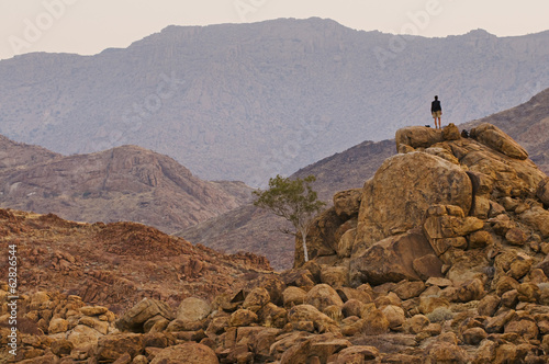 A person standing on a rock pile overlooking Brandberg, Tsiseb Conservancy, Damaraland, Namibia
