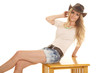 woman light shirt hat shorts sit hand by head