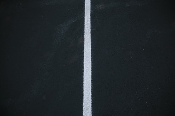 White centre line on a black asphalt surface.