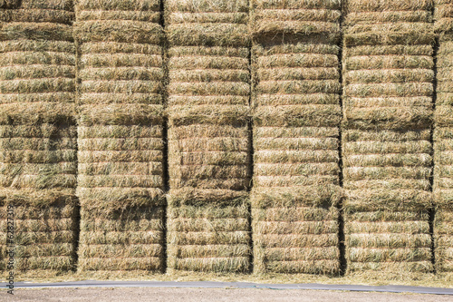 A stack of hay bales, stored in layers, to protect and keep the fodder material dry.